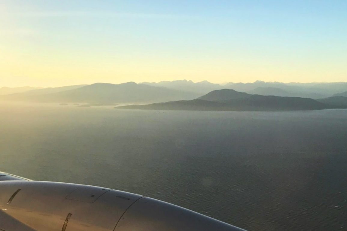view from airplane window with curvature of an engine and sunlight on distant mountains