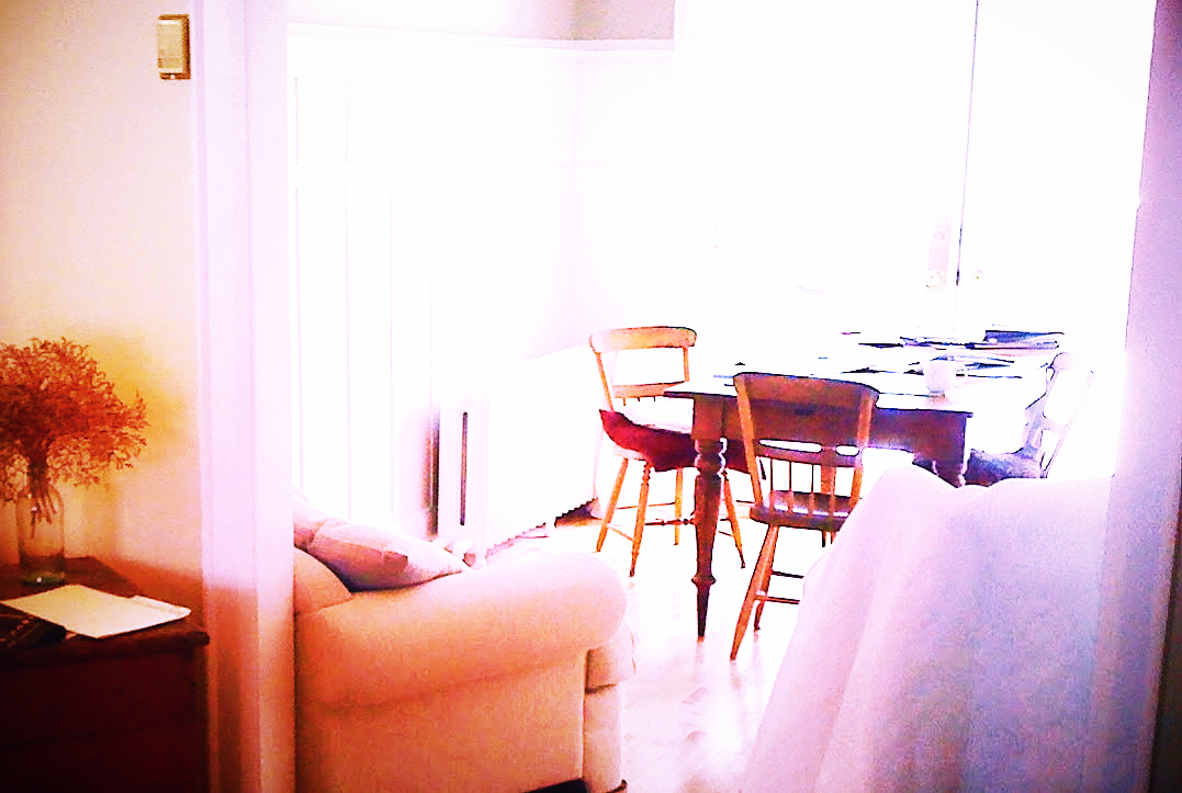 overexposed image of dining room with pine harvest table and chairs