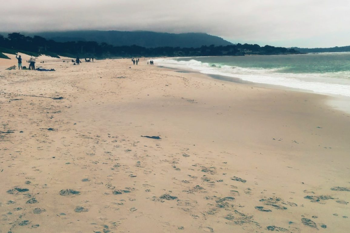 wide sandy beach in Carmel, California, as waves roll in