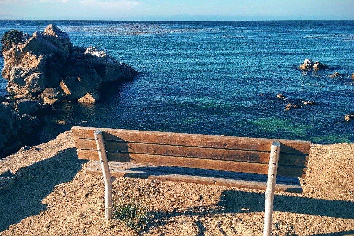 park bench overlooking ocean blue waters