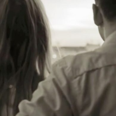 man with his arm around woman's shoulder as they look out window