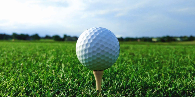 white golf ball on a yellow tee stuck in green grass