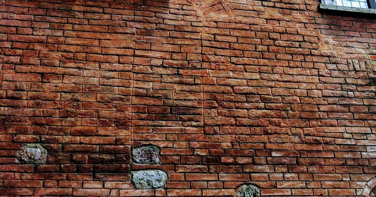 weathered rust-color brick wall with many bumps and imperfections