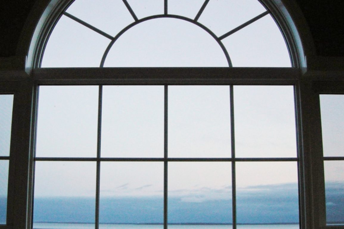 arched, multi-paned glass window overlooks ocean