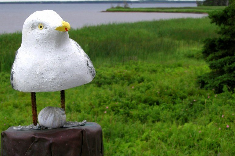 handmade seagull with yellow eyes and beak sitting atop a post