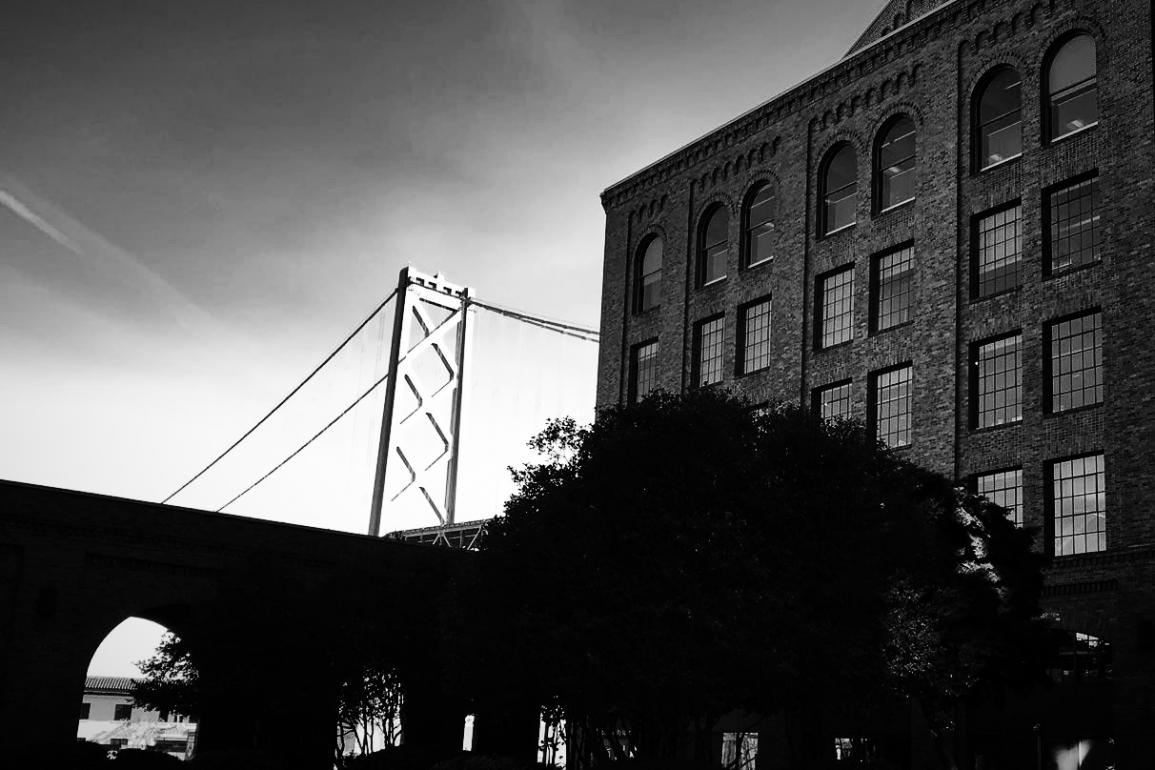gleaming bridge behind old warehouse