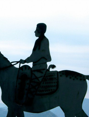 silhouette of man on horseback against pale blue sky