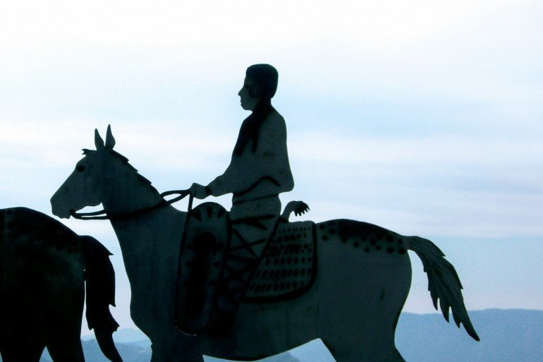 silhouette of man on horseback against pale blue sky