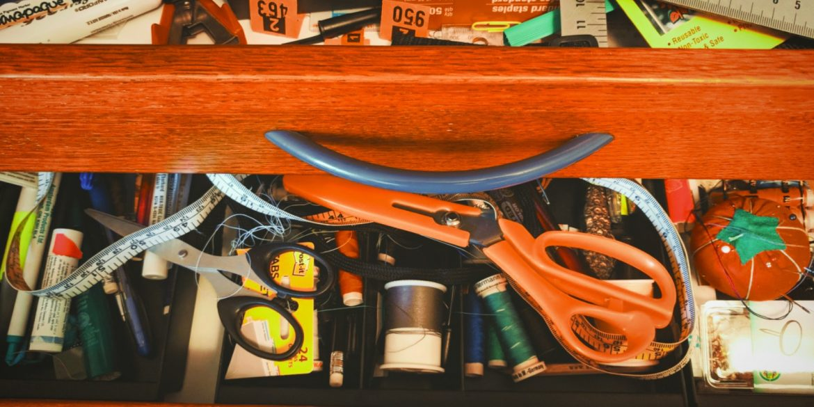 messy drawer half open to show orange scissors, measuring tape and spools of sewing thread