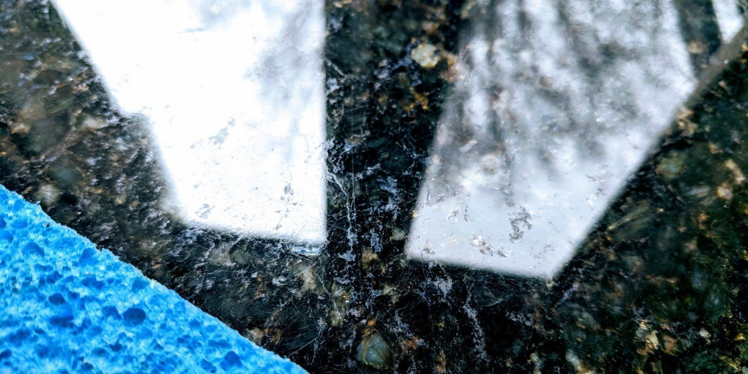 blue sponge on black granite kitchen counter with window reflections