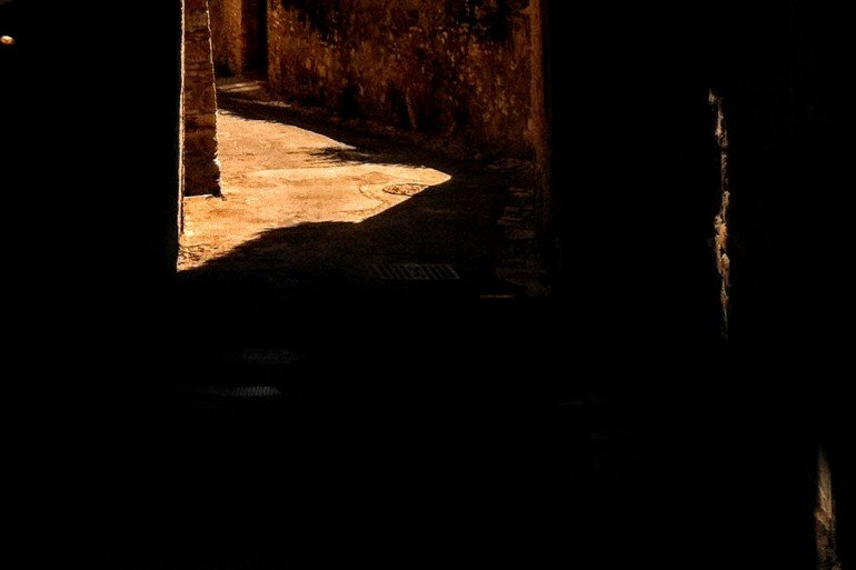 patch of light on dirt floor with dark stone walls all around