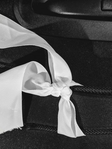 white ribbon tied onto black travel bag