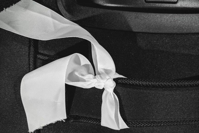 white ribbon tied onto black travel bag