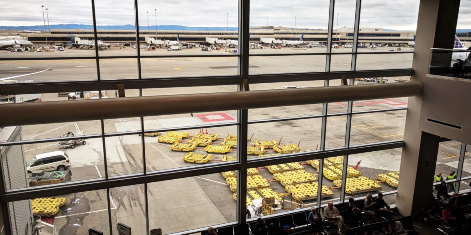 looking out large window onto tarmac at airport with airplanes parked in distance
