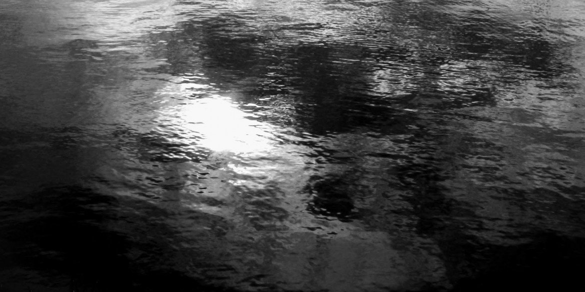 oily black water with light reflecting on surface
