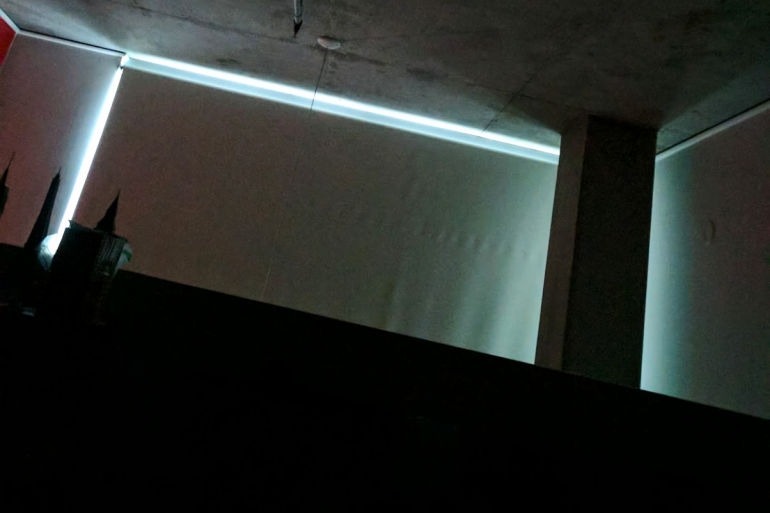 light seeps through blackout blinds in apartment at night