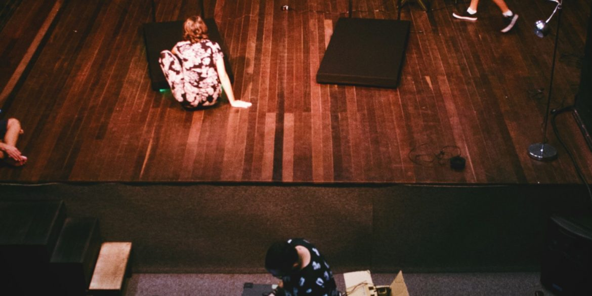 woman in floral dress sits on stage while director looks down at script