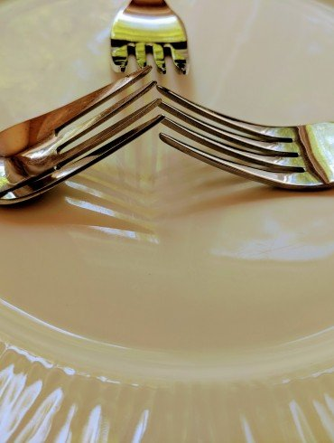 two forks on white dinner plate, with tines touching