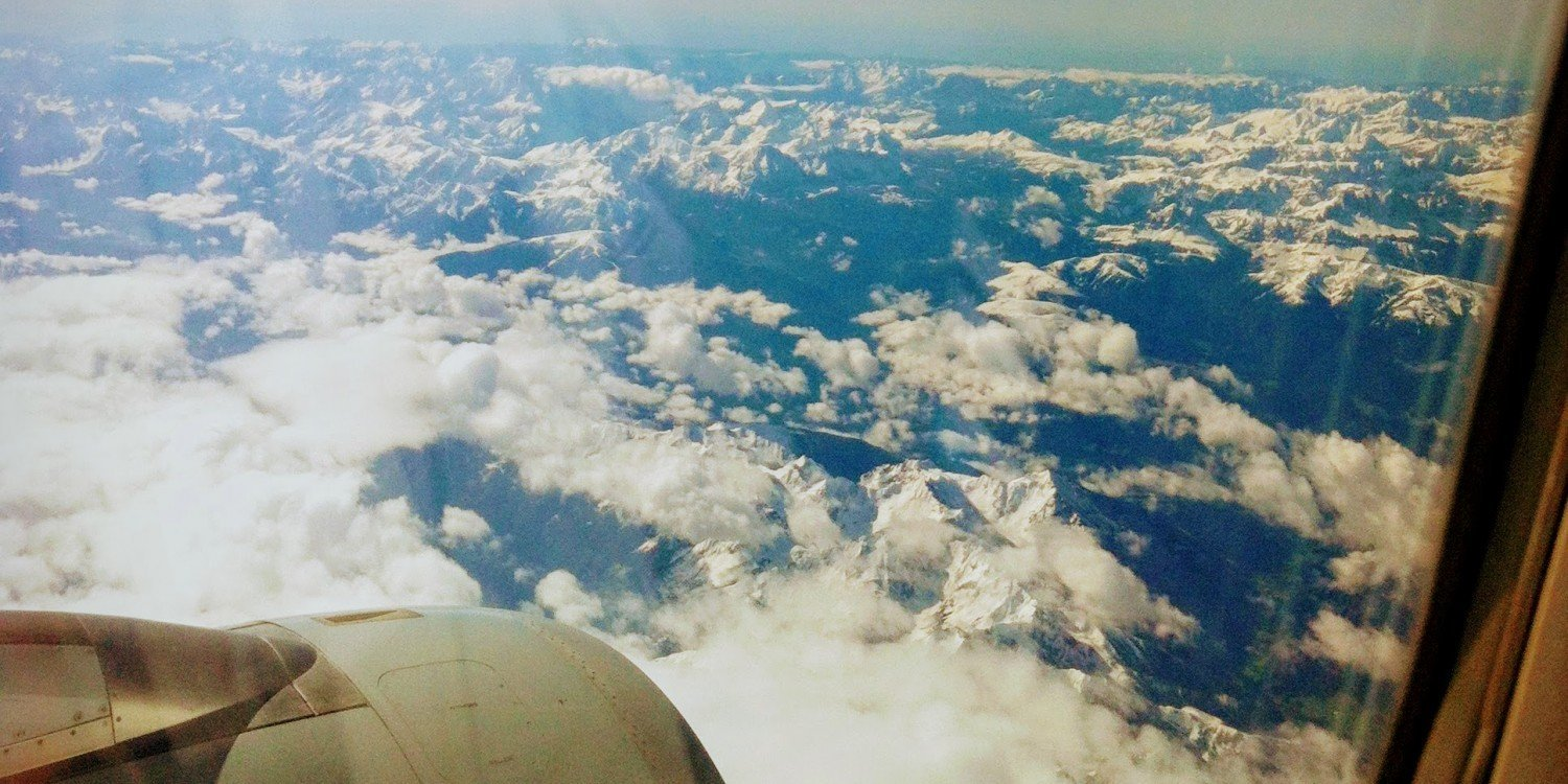 looking out airplane window at engine and white clouds and mountaintops below