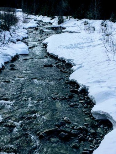 fast stream runs between snowy banks