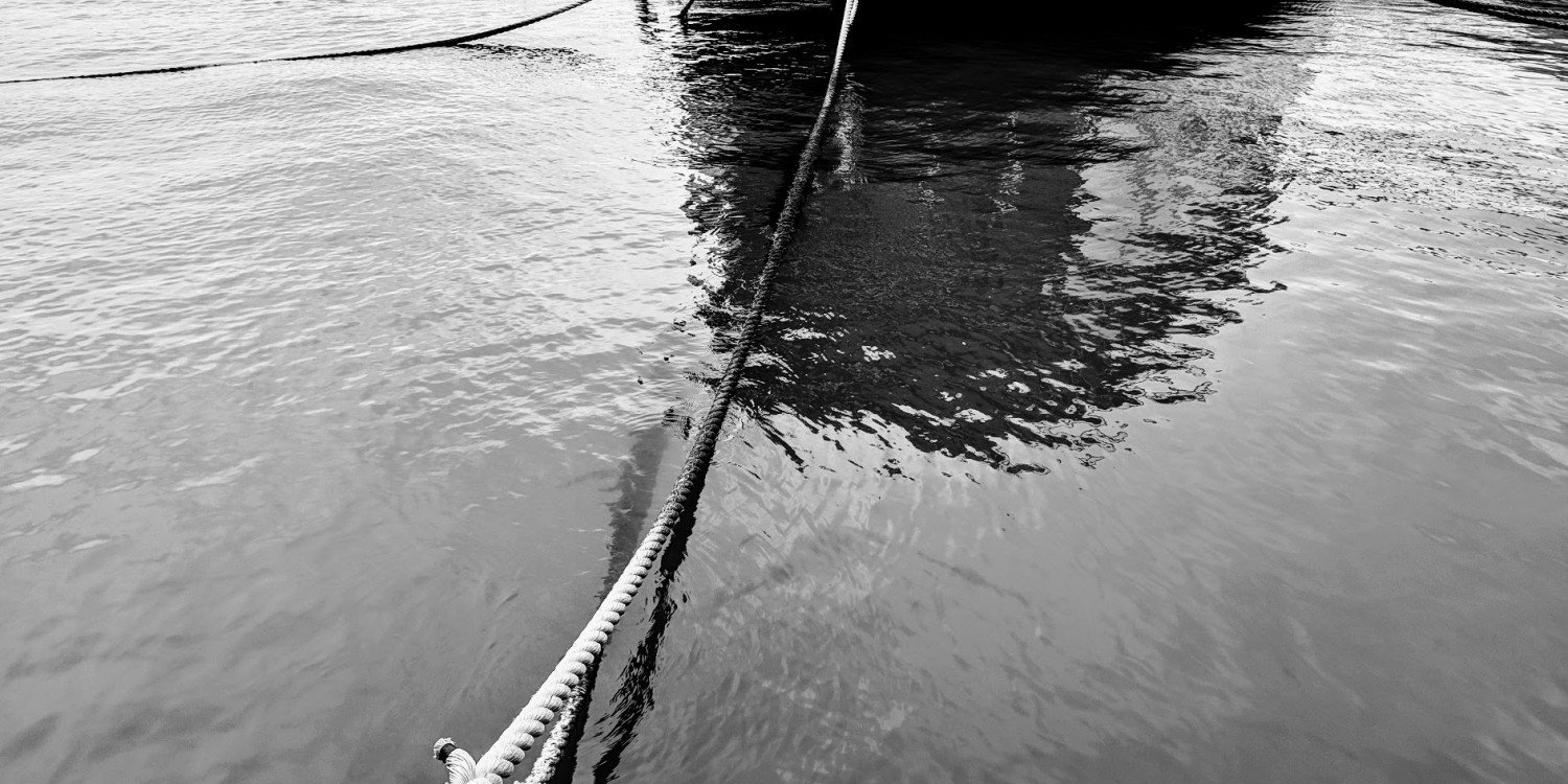 a thick rope extends across the water, tying an unseen boat to dock