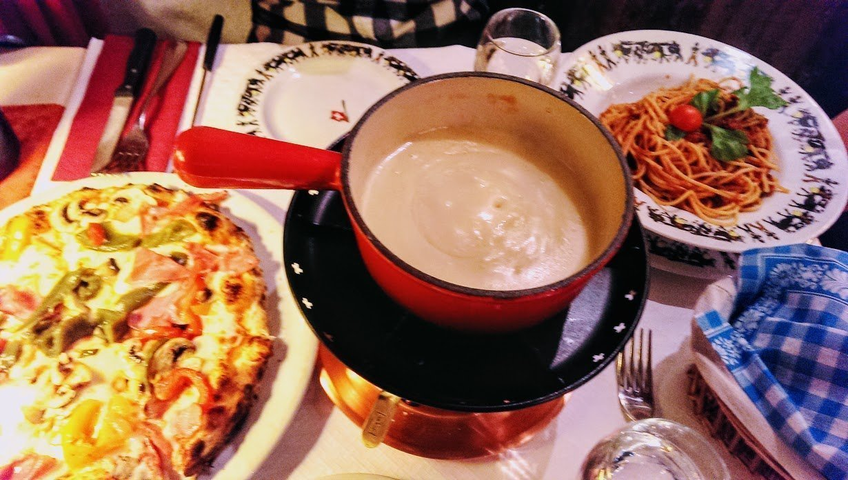 crockpot full of hot cheese on table with pizza and spaghetti