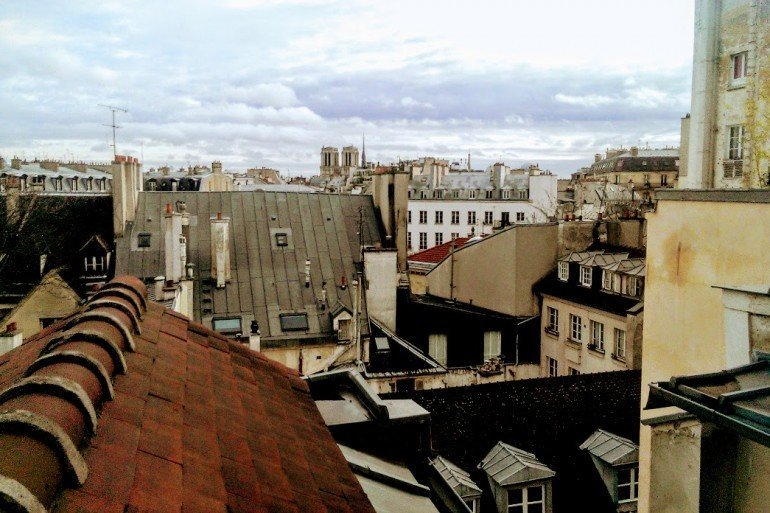 view from an 5th floor window in Paris shows jumble of nearby rooftops and distant buildings