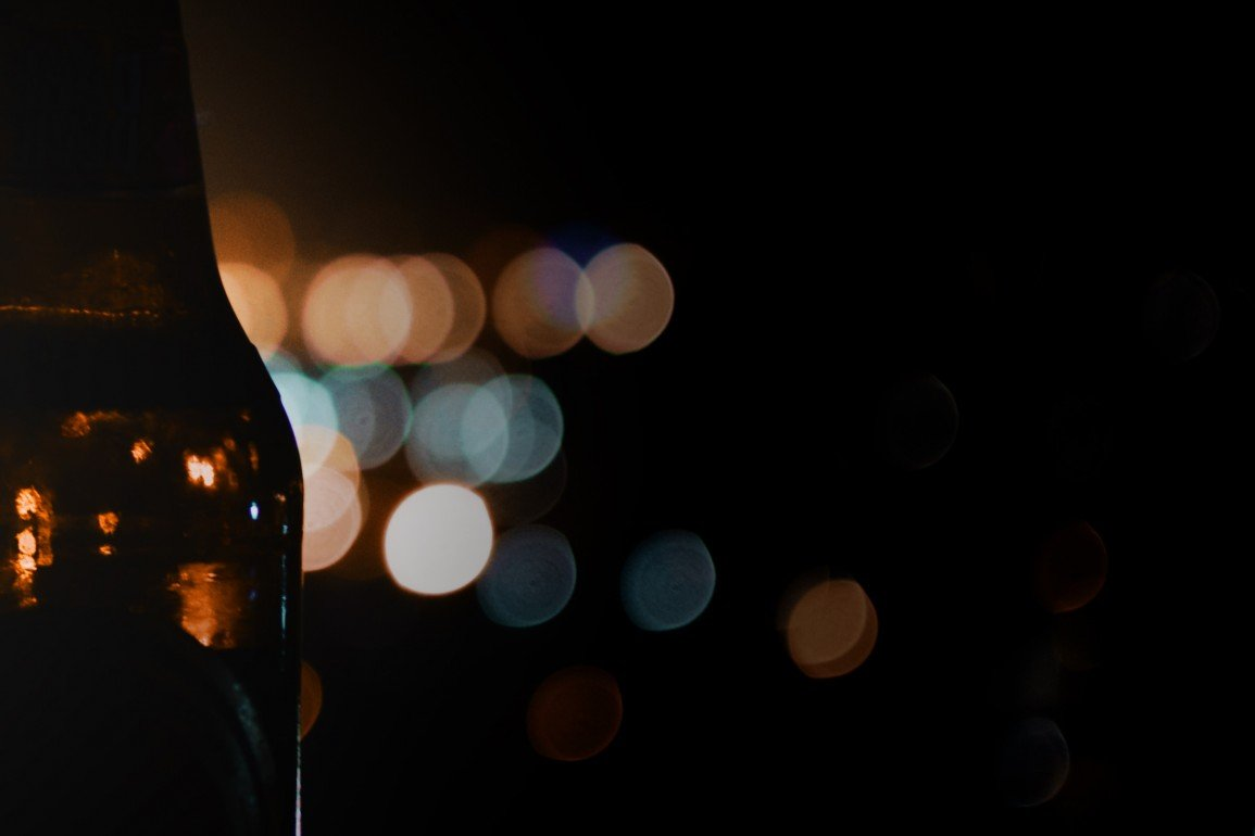 beer bottle in the dark, with light refracting behind and through