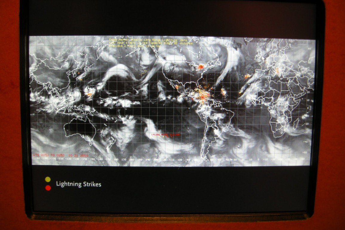 monitor displaying global weather map with grid overlay, white clouds and orange hotspots