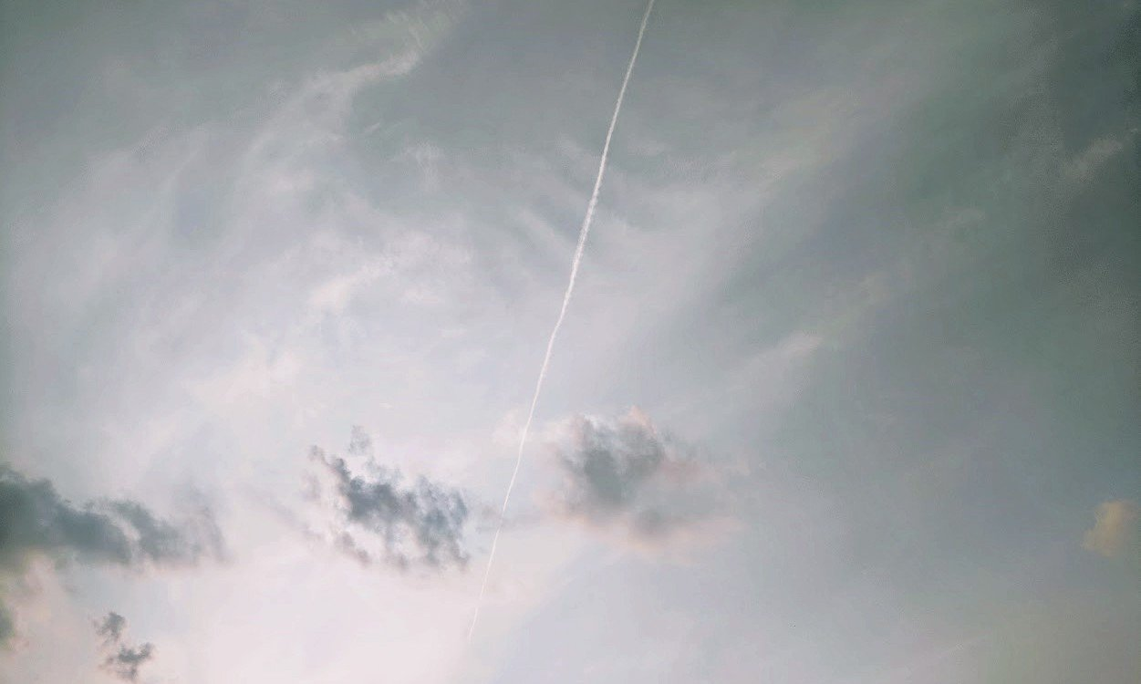 clouds in a grey sky with a jet contrail