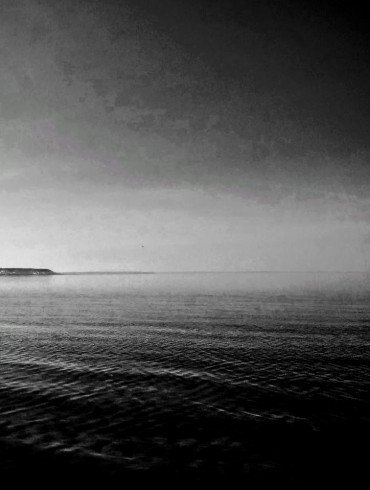 dark flat water, darkly menacing sky, a distant spit of land extends into the ocean