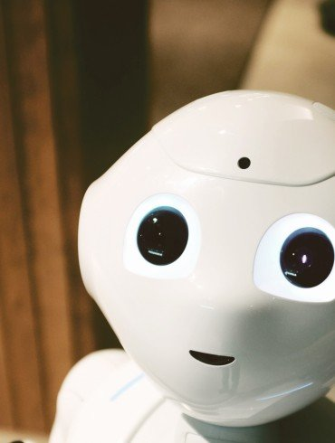 friendly, white, shiny robot's face, with big black eyes wide open looking at us, no nose and tiny mouth