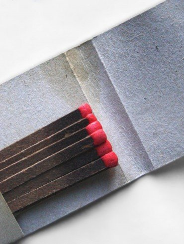 old grey matchbook half full of black matches with red striking tips