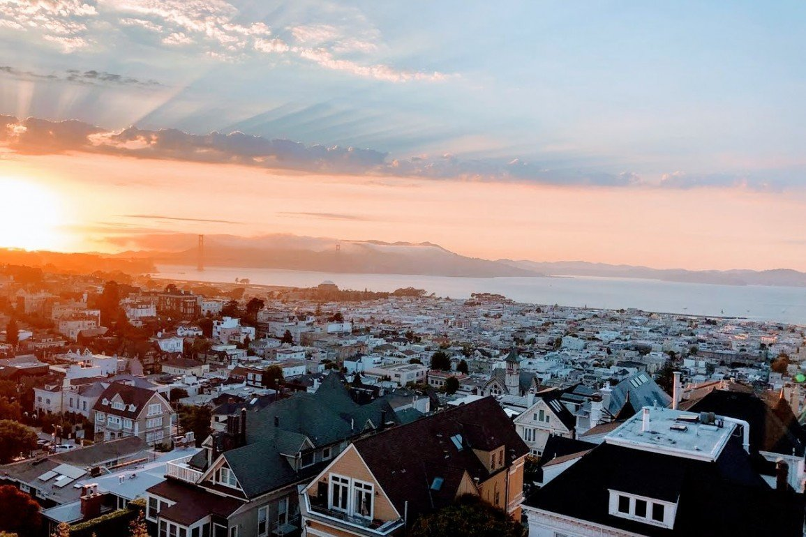 distant view of Golden Gate Bridge at sunset, seen across rooftops of houses
