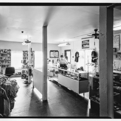 woman behind counter of a neatly organized thrift shop, empty of customers