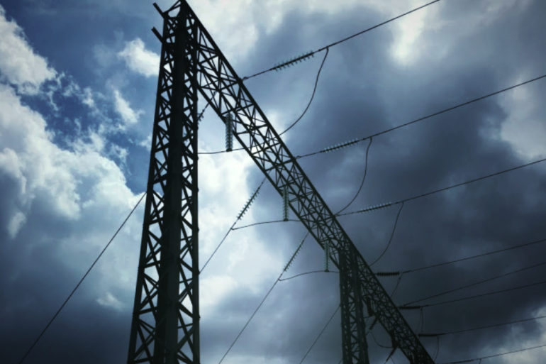 electrical grid with towers and power lines against a dark sky