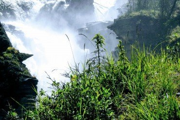 water spray and mist from a rocky waterfall with green grass in foreground