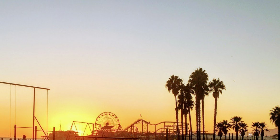ferris wheel and roller coaster at sunset