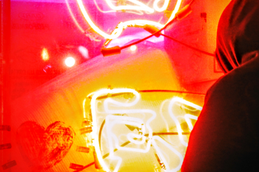 hooded figure looks at bold orange and yellow neon lights