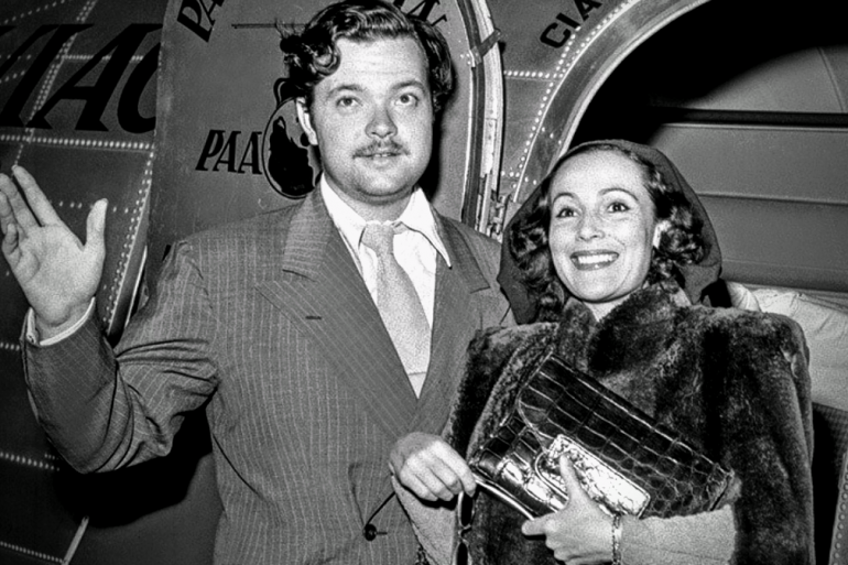 Actors Orson Welles and Dolores del Rio in doorway to airplane in 1941, Orson waves at us and Dolores smiles