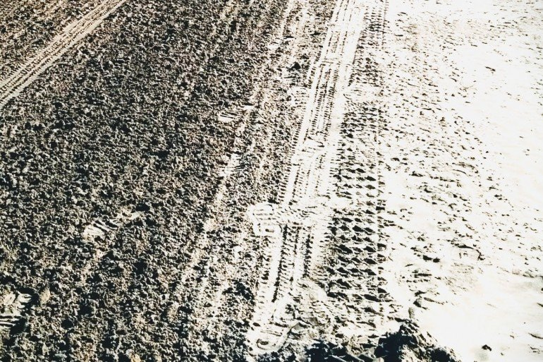 tire tracks and footprints in tightly packed dirt