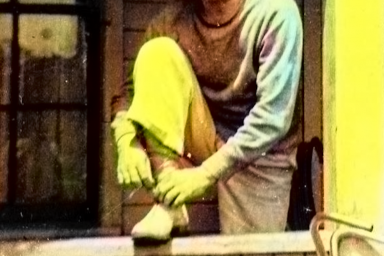 old family photo with scratches and shifted colors, shows man tying shoe