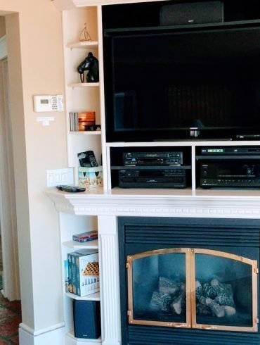 interior of a house with big screen TV and stereo above gas fireplace