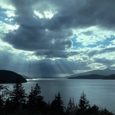 Heavenly light pierces dark clouds to illuminate a dark bay surrounded by mountains and evergreen trees