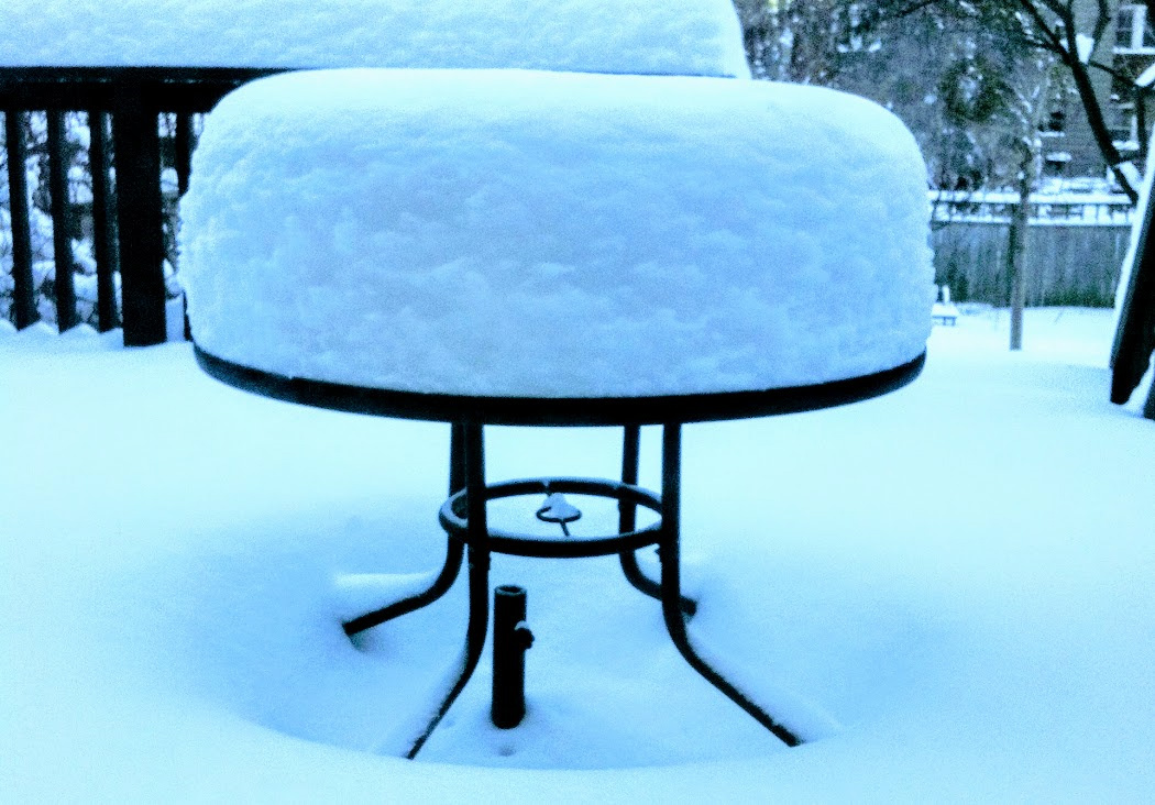 patio table with 18 inches of snow on it after a snowstorm