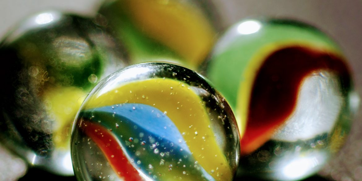 close up of glass toy marble in blue, green, red and yellow