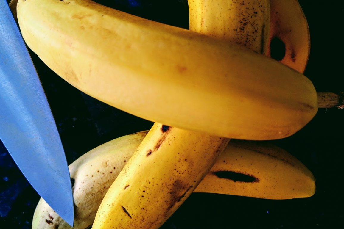 Several ripe yellow bananas with a large knife blade
