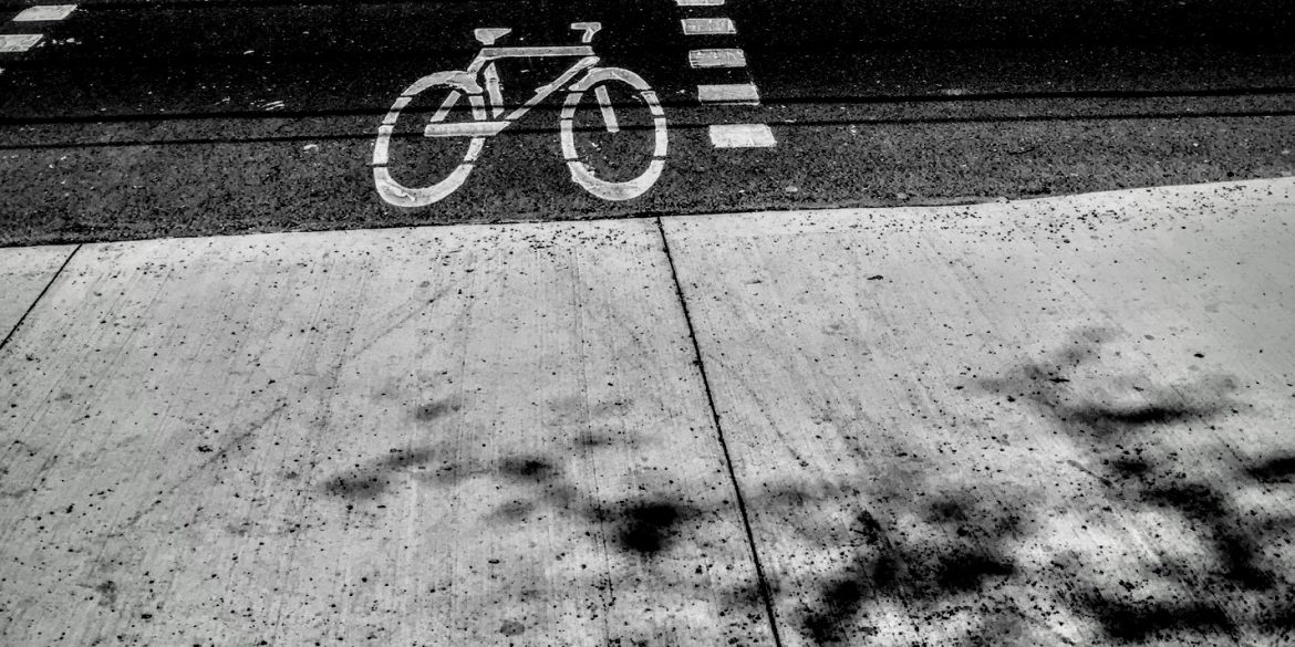white bicycle outline painted on pavement to indicate bike lane