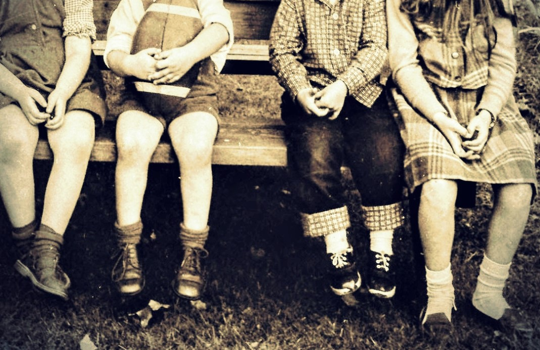 Old sepia photo of four children wearing 1960s clothing and sitting on bench