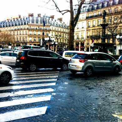 cars drive by on a busy cobblestone street in Paris